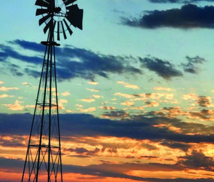 Windmill silhouetted against colorful sky