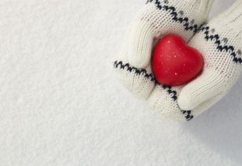 Winter background, close up of little girls hands holding red rubber heart with copy space