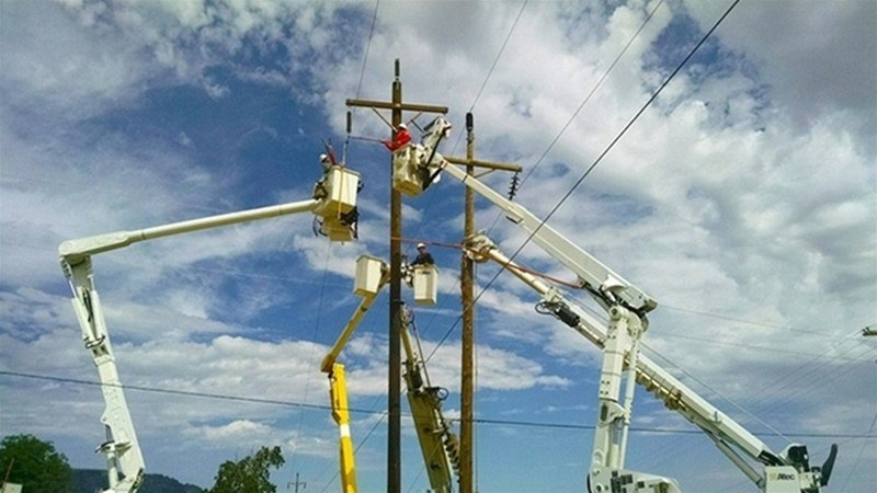 Photograph of several utility workers in raised buckets working on electric equipment across several poles
