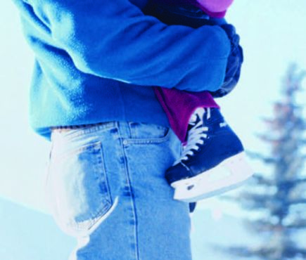 A man hold his child. Both are dressed in winter clothes and snow is visible on the ground.