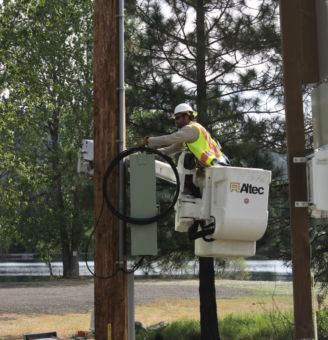 lineman doing work on power/fiber optics pole