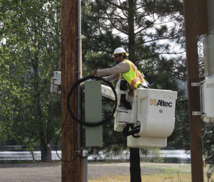 lineman doing work on power/fiber optics pole
