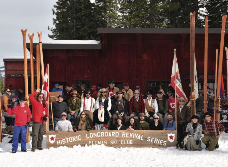 "skiers holding ""historic longboard revival series: plumas ski club"" sign in the slow, in front of wooden lodge."