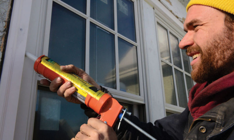 Man caulking a window