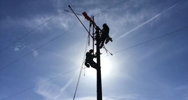 Two workers climbing on a power pole