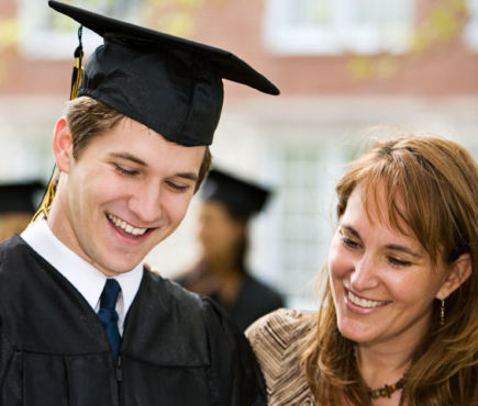 student wearing graduation cap and adult women both smiling