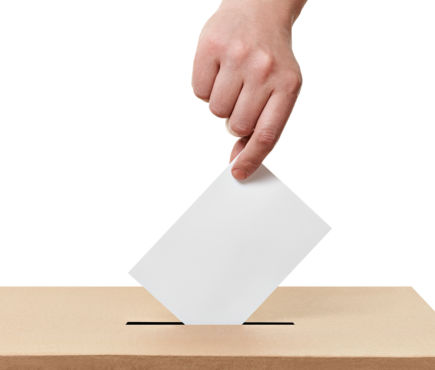 hand putting ballot in voting box